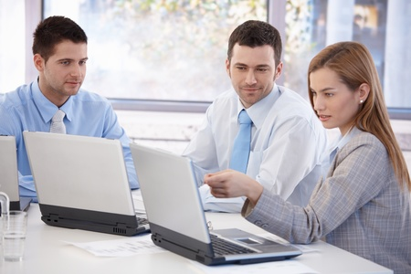 Attractive young businesspeople working together in bright office, smiling. Stock Photo - 8951338