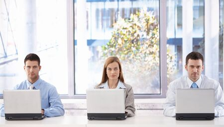 Young attractive businesspeople working on laptops individually in bright meeting room. Stock Photo - 8951252