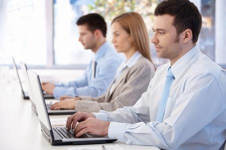Jonge ondernemers werken op laptop in lichte zaal, zijaanzicht.