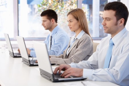 Young professionals busy by working, using laptop in meeting room. Stock Photo - 8951355