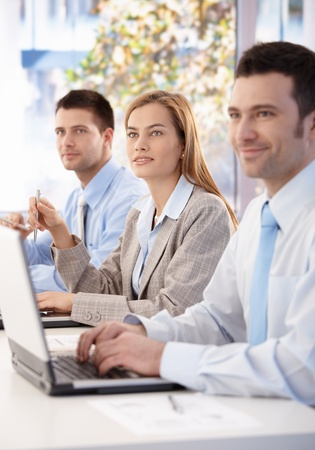 Cheerful team of young businesspeople listening presentation in meeting room. Stock Photo - 8951360