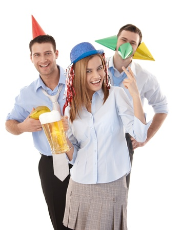 have on: Attractive young colleagues having party fun in office, laughing, wearing party hat.