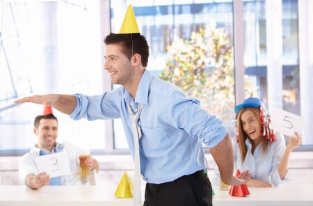 Young businessman having fun at office party, laughing.