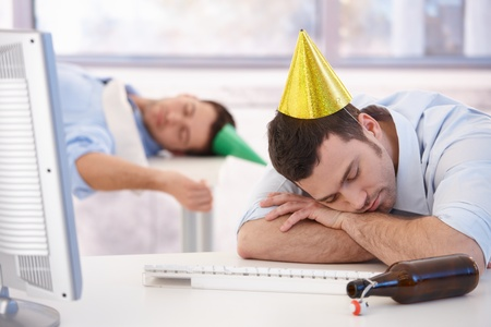 Young businessmen sleeping in office after party night. photo