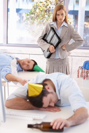 after the party: Young woman discovers sleeping colleagues in office after last night party.