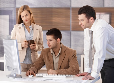 Small team of young businesspeople working together in office. Stock Photo - 8951350