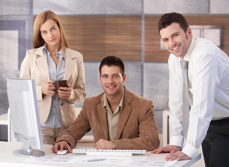 Portrait of happy businessteam working together at desk in office. photo