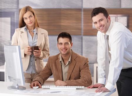 trabajador oficina: Retrato de businessteam feliz trabajando juntos en el mostrador de la Oficina.