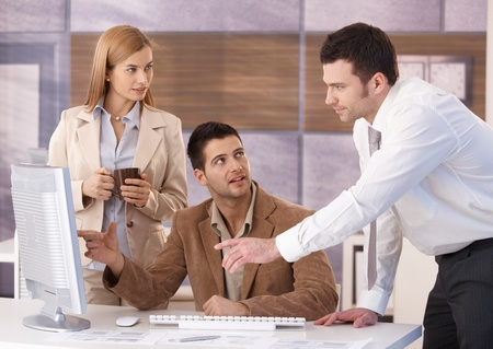co worker: Young colleagues teamworking in office, having discussion. Stock Photo
