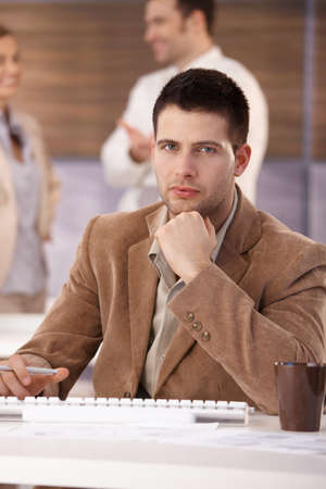 Handsome young businessman sitting at desk, working. photo