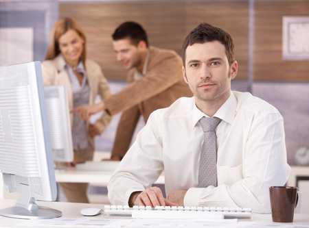 stubbly: Young handsome businessman sitting at desk at further education training.
