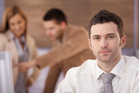 Portrait of handsome confident businessman sitting in office, colleagues talking in background. Stock Photo - 8951354