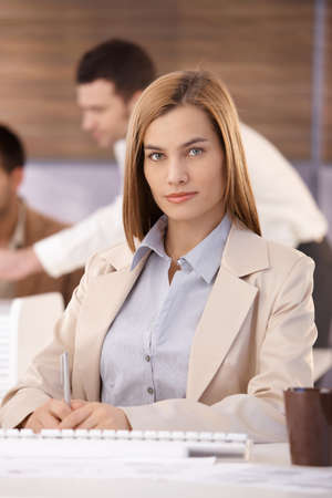 good shirt: Portrait of confident young businesswoman sitting at desk.