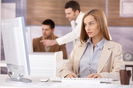 Pretty businesswoman sitting at desk, working on computer, team working in background. Stock Photo - 8951332