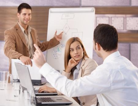 preguntando: Felices empresarios j�venes con formaci�n empresarial en la sala de reuniones. Foto de archivo