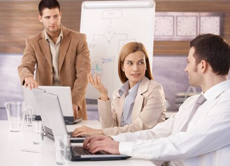 Young attractive businesswoman sitting at meeting with colleagues. photo