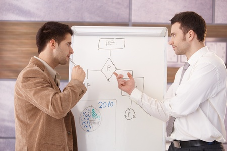 whiteboard: Young businessmen presenting together over whiteboard. Stock Photo