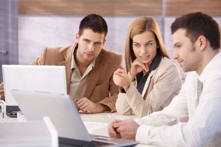 teamworking: Young attractive businesspeople teamworking in meeting room. Stock Photo
