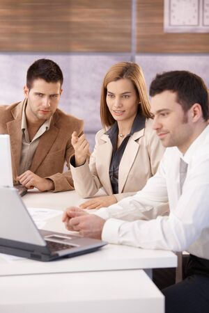 professionals: Young attractive businesspeople working together using laptop, sitting at meeting table Stock Photo