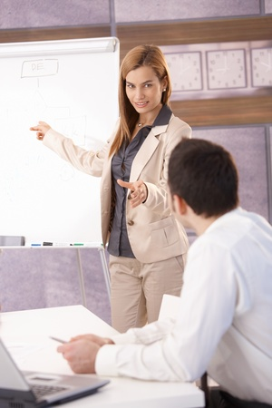 Attractive young businesswoman presenting to colleague over whiteboard, smiling. photo
