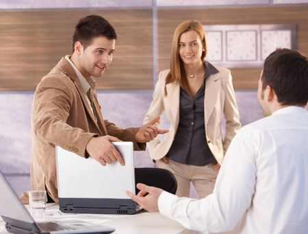 Young attractive businesspeople talking in office, smiling. photo