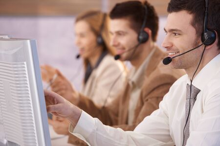 dispatcher: Young people working in call center, using headset and touch screen, smiling.
