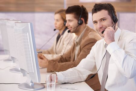 call center representative: Young cheerful customer servicer working in call center, smiling. Stock Photo