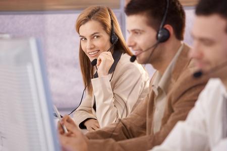Pretty female dispatcher working in callcenter smiling. photo