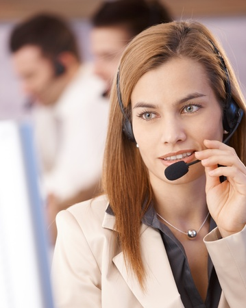 headset woman: Portrait of attractive young female dispatcher smiling in call center. Stock Photo