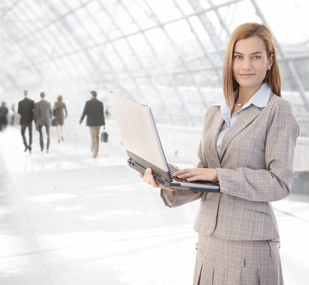 Attractive young businesswoman using laptop at office lobby, smiling. Imagens