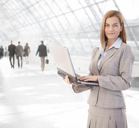 Empresaria jóvenes atractiva mediante el ordenador portátil en el vestíbulo de la Oficina, sonriendo. Foto de archivo