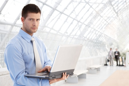 Handsome young businessman working on laptop at modern office lobby. photo