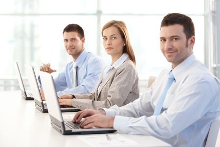 jornada de trabajo: Empresarios j�venes trabajando en equipo port�til en la Oficina brillante, sonriendo.