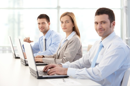 Young businesspeople working on laptop in bright office, smiling. Stock Photo - 9066108
