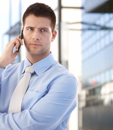 talking businessman: Guapo empresario confianza hablando por tel�fono m�vil en el barrio de negocios.