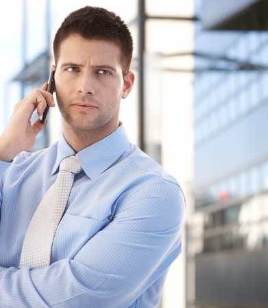 Handsome confident businessman talking on mobile phone in business quarter. photo