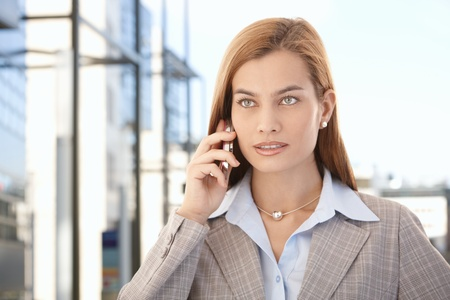 Beautiful young businesswoman talking on mobile phone in business quarter. Stock Photo - 9066120