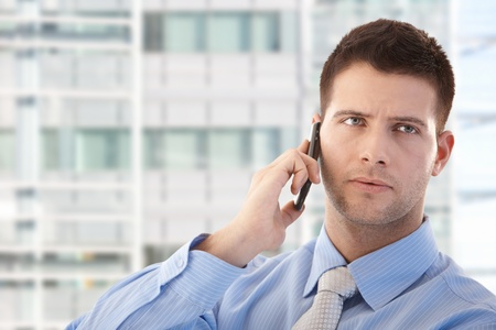 Handsome young businessman using mobile phone in modern office front of window.