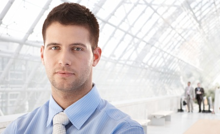 businessman: Portrait of handsome young businessman standing in office lobby.