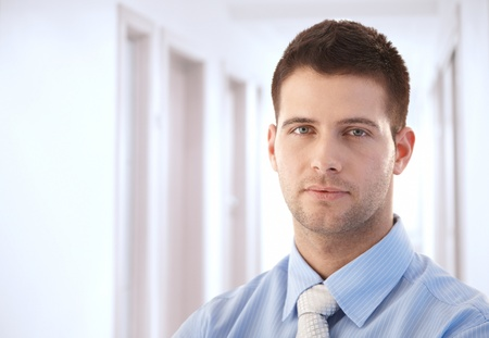 serious guy: Goodlooking young businessman standing in hallway.