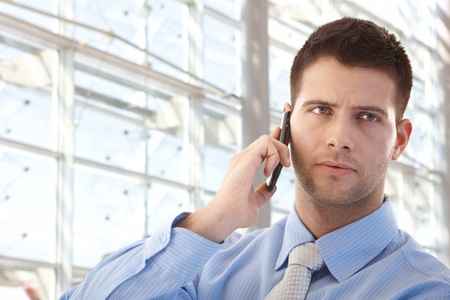 Handsome young businessman talking on mobile phone front of window in bright office. Stock Photo - 9066121