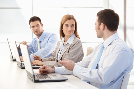 Young team of attractive businesspeople working together in bright office.