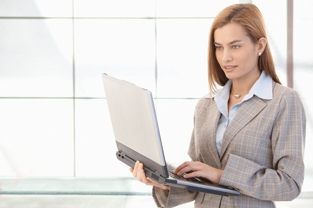 Attractive young businesswoman working on laptop, smiling, standing in office. photo