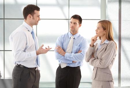 prestar atencion: Trabajadores jóvenes atractivas Oficina casual hablando en el pasillo.