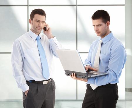prestar atencion: Jóvenes empresarios permanente en el vestíbulo de oficina, uno en el teléfono, el otro trabajo en equipo portátil. Foto de archivo