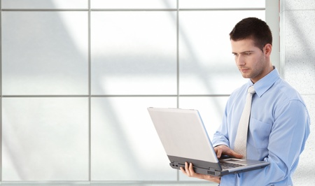 copyspaces: Young goodlooking man using laptop in office lobby, standing. Stock Photo