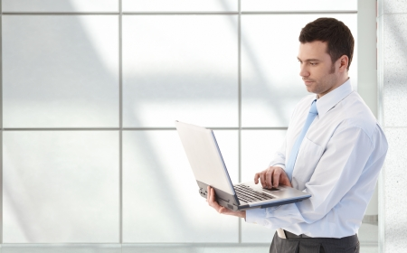 severity: Young businessman working on laptop, standing in office lobby.