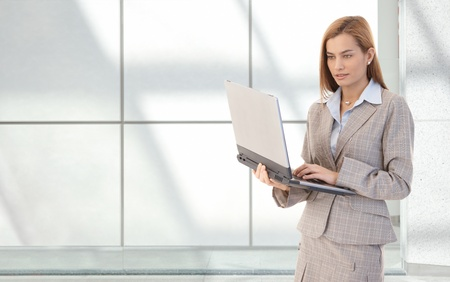 Attractive businesswoman standing in office lobby with laptop in hands, working, smiling. photo