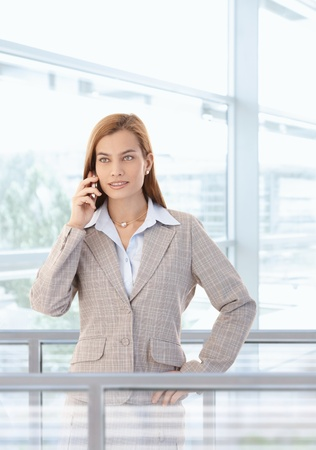 Attractive young businesswoman talking on mobile phone, standing in bright office lobby. photo