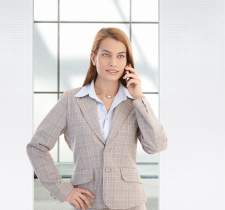 Young confident businesswoman talking on mobile phone, smiling. photo